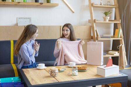 Look what I get. Excited caucasian girl boasting in front of her friend, showing new sweater, cafe interior, copy space