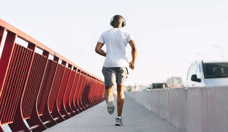 Athletic Black Man Running On Bridge, rear view, copy space