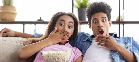 Frightened african american teenagers watching scary movie at home and eating popcorn, panorama