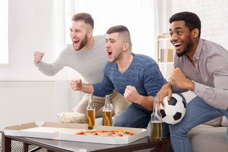 Football fans watching match and shouting at home, cheering for favourite team, free space Stockfoto