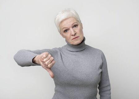 Dislike. Upset senior woman showing thumb down gesture as rejection symbol