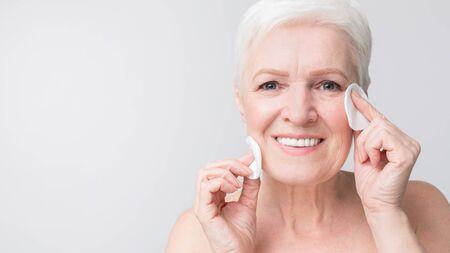 Portrait of charming senior woman cleansing her face from makeup using cotton pads. Closeup panorama with copy space