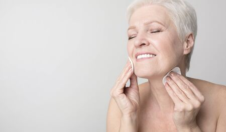 Attractive senior woman enjoying her beauty and face care routine, cleansing skin with cotton pads. Panorama with copy space