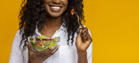 Healthy food concept. Smiling black lady eating fresh vegetable salad, yellow studio background, copy space