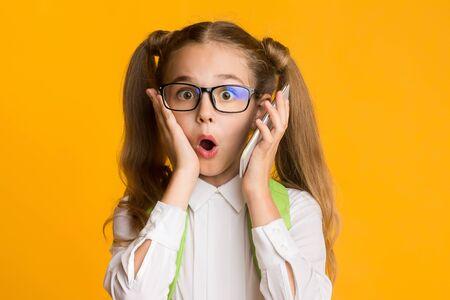OMG, Mobile Phone Addiction. Shocked Little School Girl Holding Smartphone To Ear On Yellow Studio Background. Empty Space