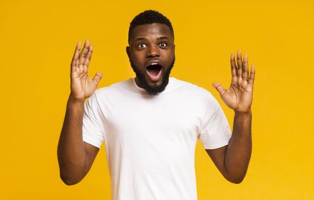 Surprised and shocked african american guy opened mouth in amazement, yellow studio background