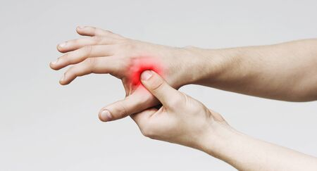 Acute pain in male palm. Man holding hand to spot of palm-ache, panorama