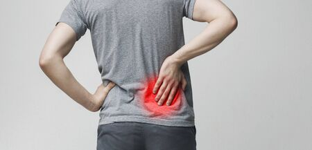 Lumbago symptom. Young man holding his painful inflamed loin, panorama, empty space