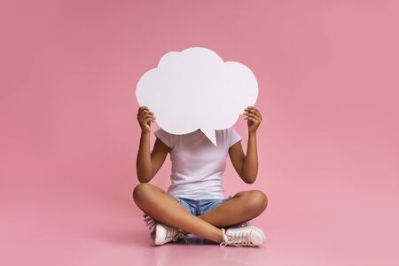 Empty speech bubble at black teenager hands. Girl sitting with crossed legs at pink studio background