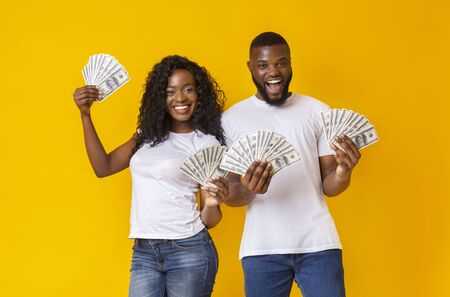 We are in luck. Cheerful Black Couple Holding Money, yellow studio background