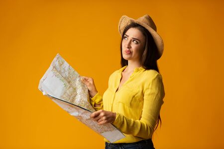 Vacation Plans. Traveler Girl Holding Map Planning Next Trip Itinerary Over Yellow Background In Studio, Copy Space