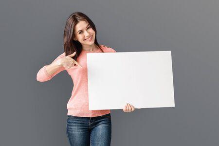 Junge kaukasische Frau, die weiße leere Karte hält und auf leeres zeigt