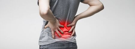 Man holding his hands behind his back, pain in spine, touching red inflamed zone, panorama Stockfoto
