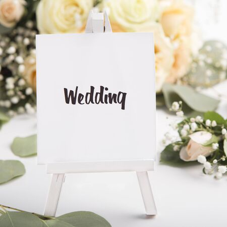 Close up of wedding concept on small easel on creative background with roses