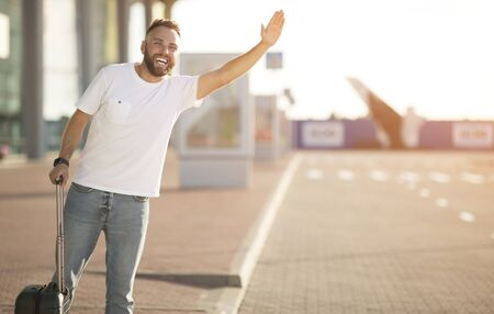 Catch taxi. Young man standing near airport terminal, raising hand, empty space
