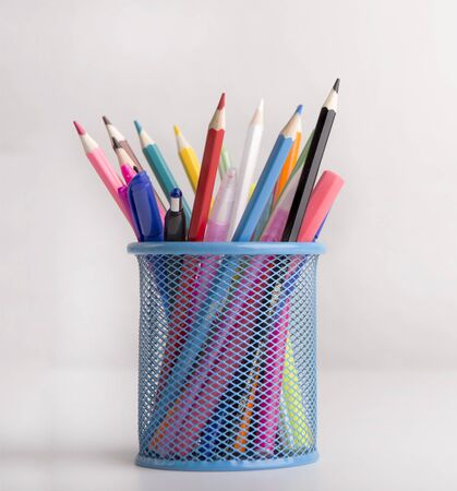 Close up of colored pencils in blue transparent stand on white background with shadow