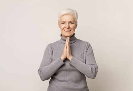 Beautiful senior woman pleading for something with clasped hands. Light studio background with copy space Foto de archivo