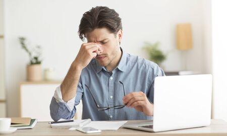 Ogen vermoeidheid. Vermoeide man die zijn neusbrug masseert en een bril vasthoudt die op een laptop in kantoor zit