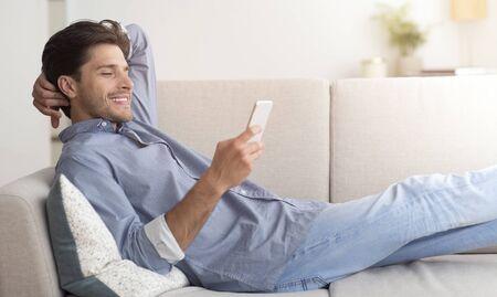 Lächelnder Mann Mit Smartphone Zu Hause Auf Sofa Liegend. Freier Platz für Text