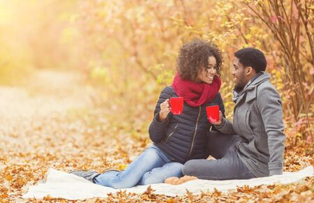 Young couple enjoying picnic in autumn park, drinking coffee and enjoying time, free space