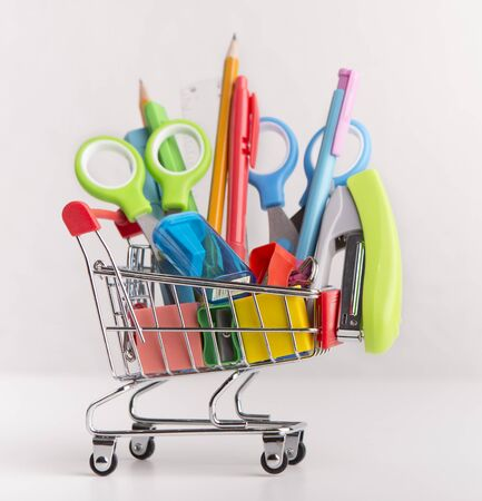 Close up of shopping cart with purchases from stationery shop, white background, sale concept