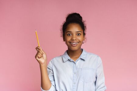 Education and inspiration. Teenage girl having idea, raising pencil in funny attention gesture, copy space Stockfoto