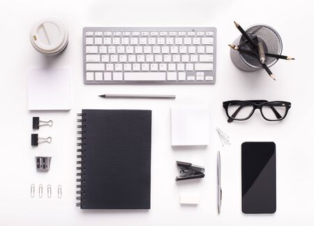 Corporate style supplies on workplace with keyboard and cellphone on white office table, blank screen for application Stock Photo