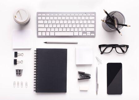 Suministros de estilo corporativo en el lugar de trabajo con teclado y teléfono celular en la mesa de oficina blanca, pantalla en blanco para la aplicación Foto de archivo