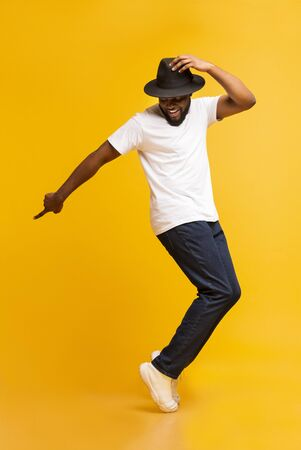 Cheerful african man dancing on tiptoes, copy michael jackson style on yellow studio background
