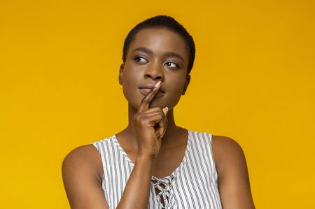 Being serious. Concentrated afro woman touching her lips while thinking, looking aside, yellow studio background
