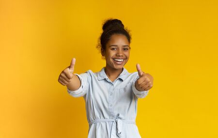 I like it. Cheerful african american girl showing thumb up and smiling at camera, yellow background