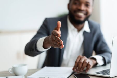 Partnership concept. Smiling young African American businessman extending hand to shake, selective focus on arm