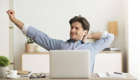 Man Stretching Hands Sitting At Laptop Excercising Tired Of Working Or Studying At Home.