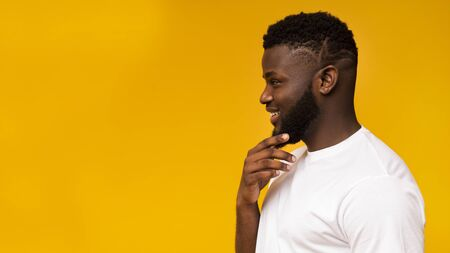 Young black guy thinking about something and looking at free space on yellow studio background, panorama