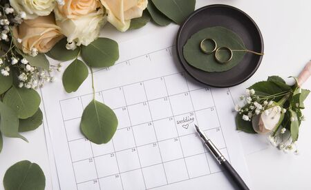 Waiting for wedding date which writing by pen in paper calendar on background with roses