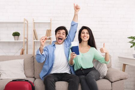 Ready for vacation. Happy couple showing passports and thumbs up, looking at camera