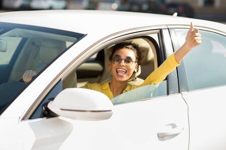 Get driving license. Happy woman showing thumb up gesture, driving car 写真素材