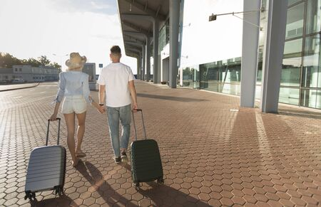 Travelling together. Couple walking near airport building with luggage, back view, free space