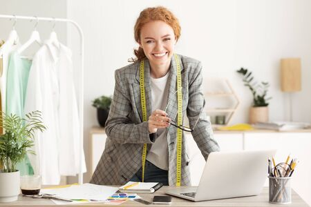 Happy designer woman work on computer in tailor workshop, smiling to camera