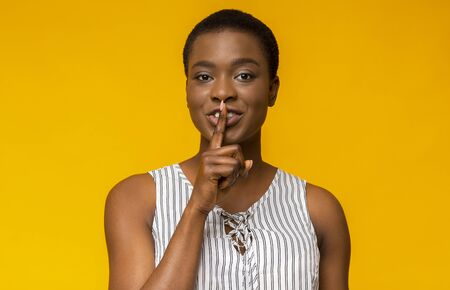 Shhh! Mysterious african american woman showing silence gesture, yellow background