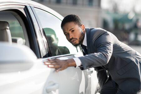 The final check. Afro man examining new car at dealership, touching doors