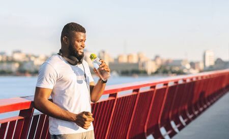 Stay Hydrated. Cheerful African American Sportsman Drinking Water On The Bridge, free space