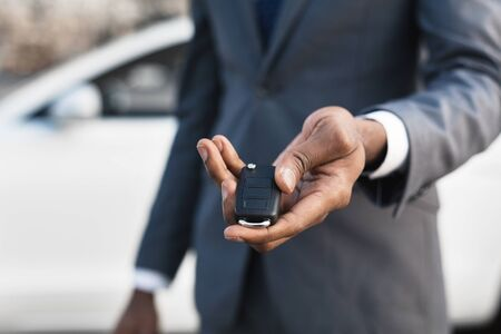 Car sale concept. Man in suit giving car key, focus on hand
