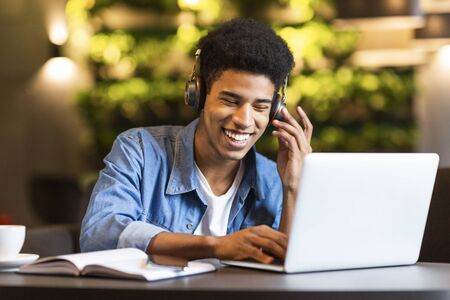 Cheerful black young guy with headset looking at laptop, having fun while studying, cafe interior Фото со стока