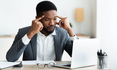 Concentrated african employee analyzing information on laptop, working in office, copy space