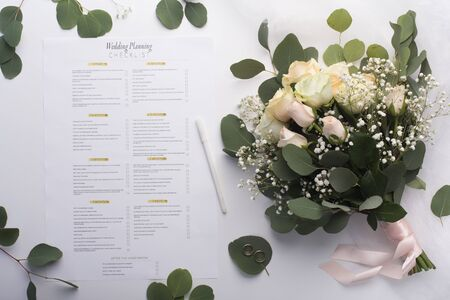 Be ready for wedding troubles. Bridal roses bouquet and planning checklist on white background