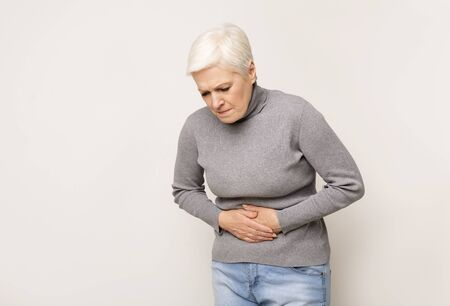 Unhappy senior woman holding stomach, suffering from abdominal pain because of food poisoning. Copy space