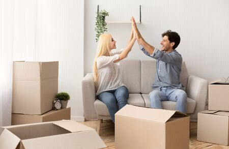 Successful Relocation. Young Couple Giving High-Five Sitting On Sofa Among Moving Boxes In New Apartment. Free Space Stockfoto