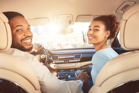 Enjoying road trip together. Young couple driving car, looking over shoulder with smile