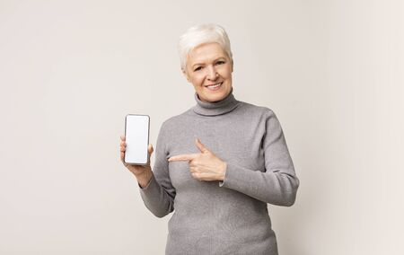 Application for seniors. Smiling mature lady pointing at cellphone with blank screen, copy space